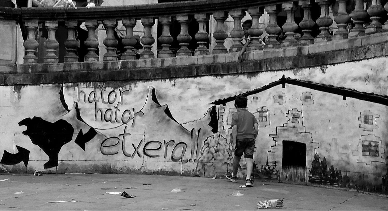 Dos niños juegan junto a un mural que reclama la vuelta de los presos de ETA a casa.