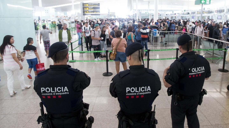 Tres mossos vigilan a los pasajeros en El Prat.