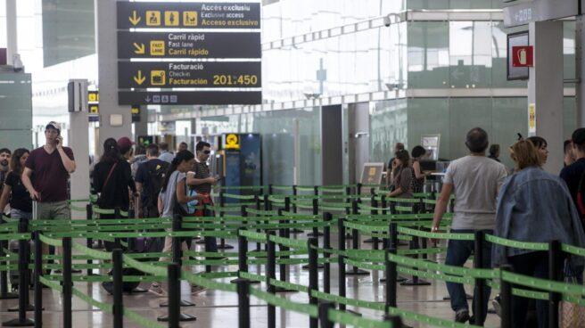 Pasajeros esperan ante el arco de seguridad en El Prat.