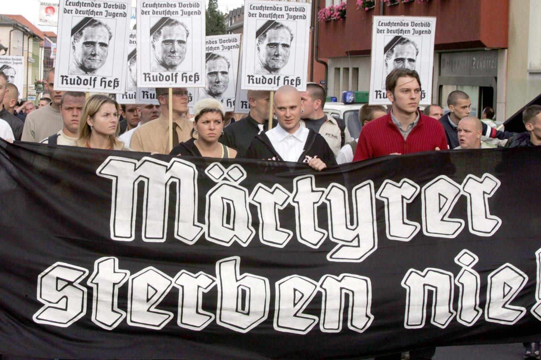 """Fotografía de archivo del 21 de agosto de 2004 que muestra a activistas de extrema derecha mientras se reúnen en las calles y sujetan una pancarta en la que se lee """"¡Los mártires nunca mueren!"""", durante una manifestación para conmemorar el 17 aniversario de la muerte de Rudolf Hess, lugarteniente del dictador de la Alemania nazi, Adolf Hitler, en Wunsiedel (Alemania). El lugarteniente nazi fue uno de los políticos más importantes del III Reich, recibiendo ese título en el año 1933"""