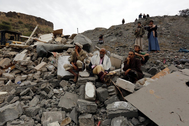 Varios yemeníes sentados entre los restos de un edificio tras un bombardeo de la coalición liderada por Arabia Saudí, en Saná.