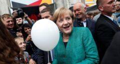 Angela Merkel recibe un globo de un niño en la campaña electoral en Berlín.