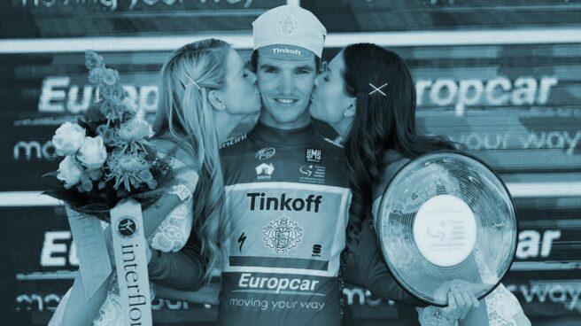 Azafatas con el ganador de una etapa en una carrera ciclista.