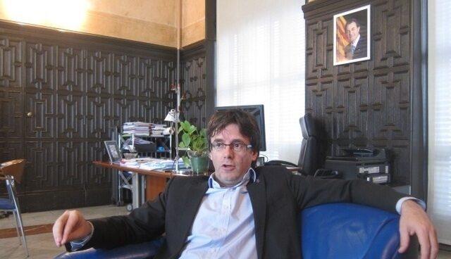 Carlos Puigdemont, en su etapa como alcalde de Girona con una foto de Artur Mas a sus espaldas.