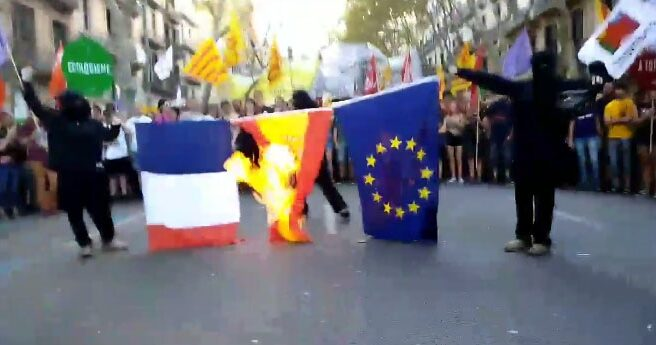 Tres encapuchados queman las banderas de Francia, España y la UE.