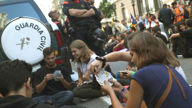 Un grupo de manifestantes, jugando a las cartas junto a un coche de la Guardia Civil.