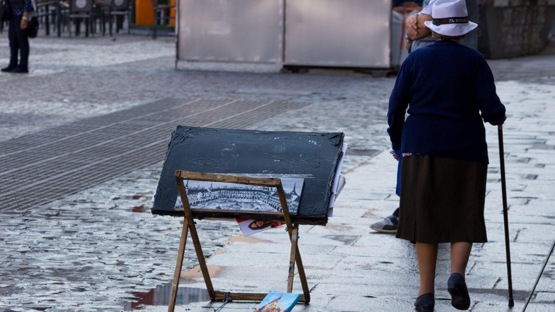 Una mujer pasea al lado de un puesto de arte.