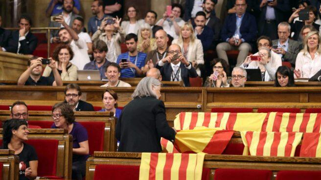 La diputada de Podem Ángels Martínez reitra las banderas de España del hemiciclo del Parlament y deja las esteladas catalanas.