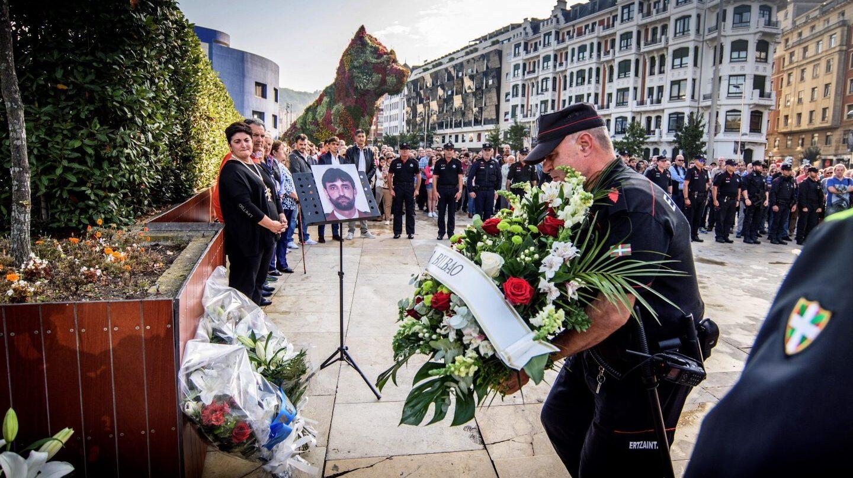 Agentes de la Ertzaintza ponen flores delante del monolito que hay en recuerdo de Txema Agirre.