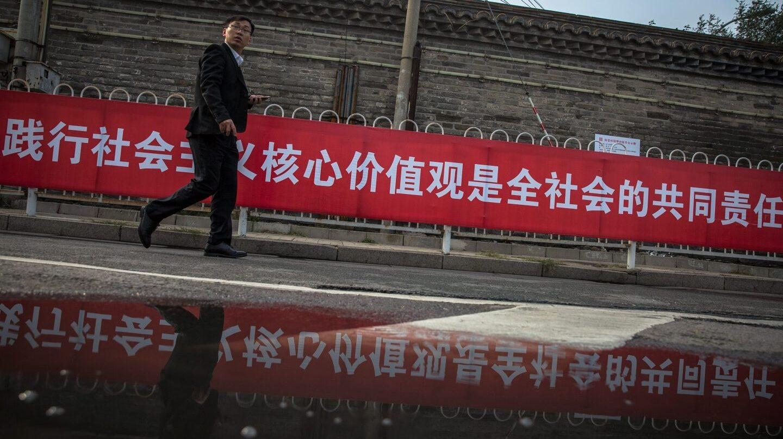 Un hombre pasa junto a una pancarta con propaganda del XIX Congreso del .Comunista de China