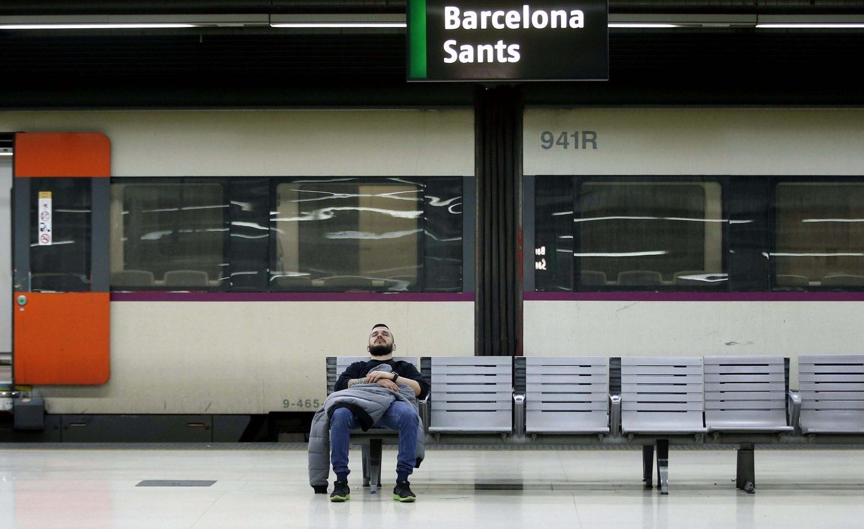 Un hombre descansa en un banco en el interior de la estación de Barcelona Sants.