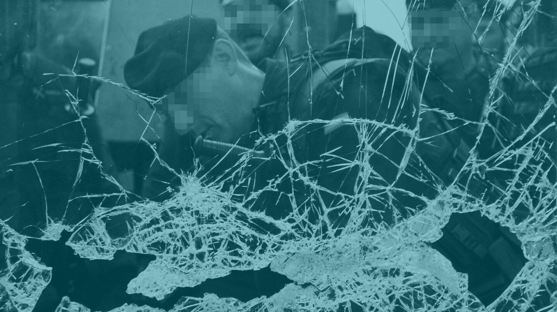 Un guardia Civil tras un cristal roto en un centro de votación.