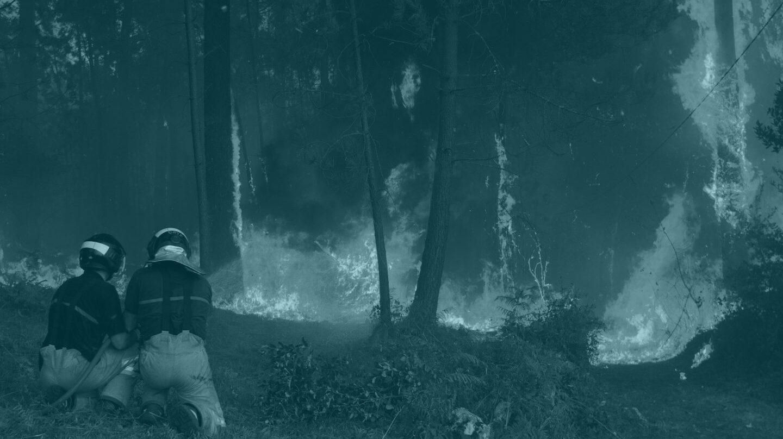 Dos brigadistas se enfrentan a uno de los incendios en Galicia.