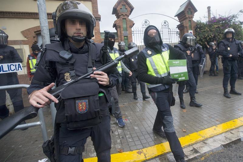 Un antidisturbios de la Policía Nacional, a las puertas de un instituto de L'Hospitalet (Barcelona) este domingo.