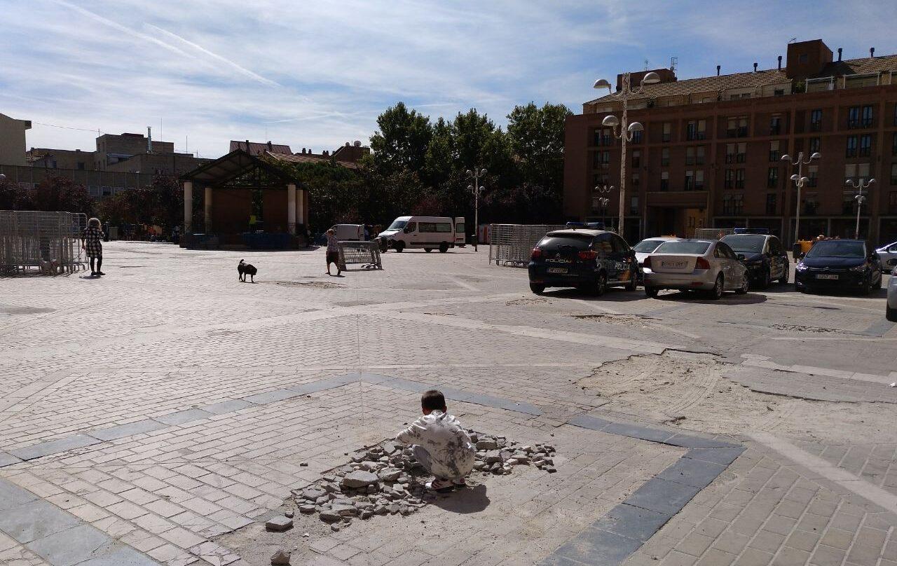 Un crío juega sobre los cascotes de un socavón en La Remonta. Junto a él, coches de policía aparcados de manera ilegal.