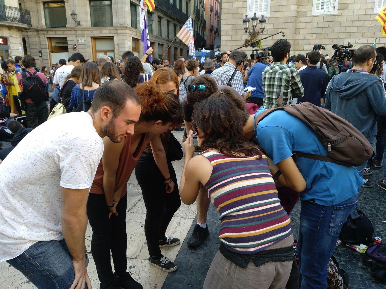 Jóvenes independentistas escuchan el discurso de Puigdemont en el que rechazó convocar elecciones.