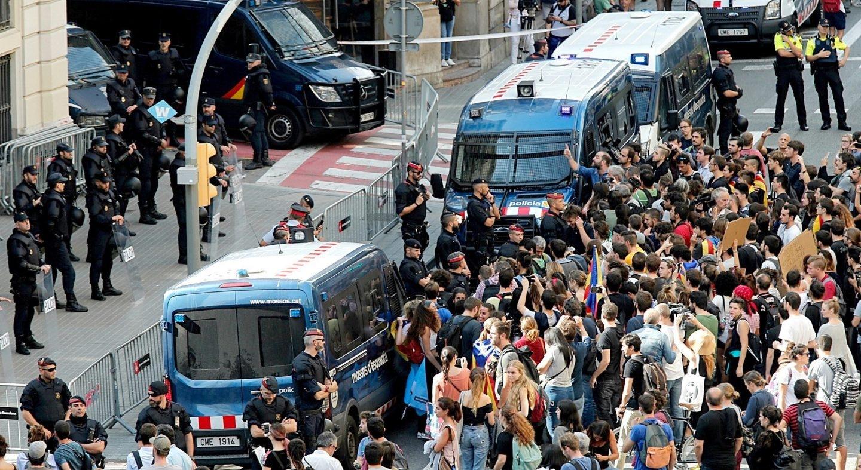 Los Mossos protegen de los manifestantes a un contingente de la Policía Nacional, en Barcelona.