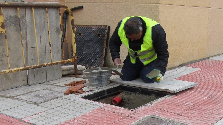 Un hombre trabaja en la reparación de una acera.