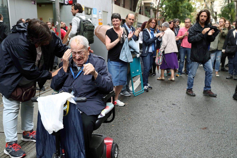 Un emocionado votante en el referéndum independentista de Cataluña aplaudido por las personas que guardan cola en la Escola Jaume I en el barrio de Sants de Barcelona.