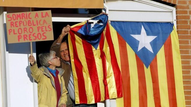 """Un vecino saca una bandera """"estelada"""" por la ventana durante la manifestación convocada en Barcelona por la ANC y Ómnium Cultural."""