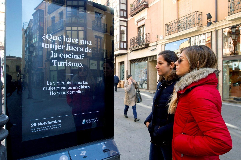 Dos mujeres contemplan un mupi con mensajes de la campaña contra la violencia de género en Zamora.