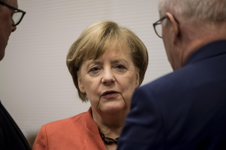 La cancilller Angela Merkel conversa con sus colaboraderes, en Berlín.