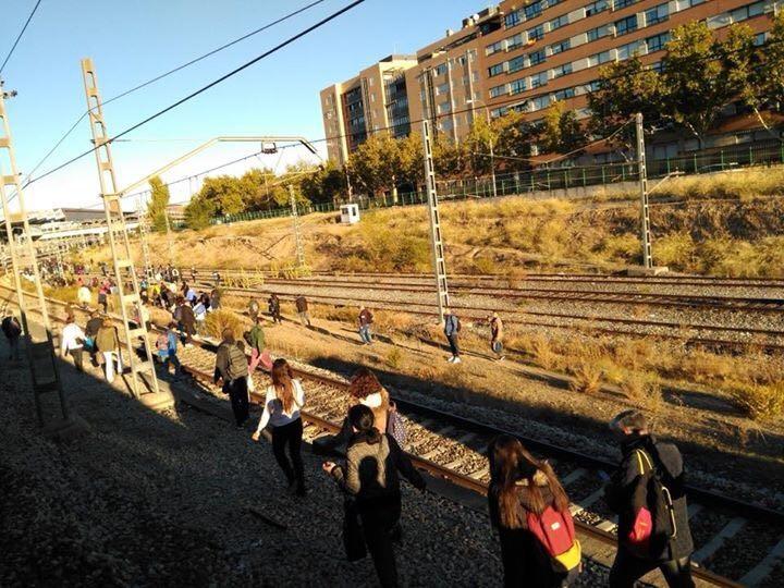 Pasajeros de un tren de Cercanías en Madrid caminan por las vías tras una avería.