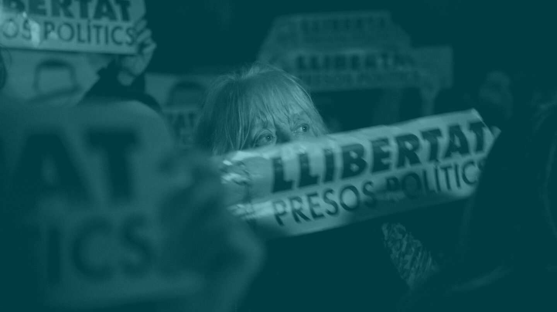 Una mujer muestra una pancarta con la palabra 'Libertad'.