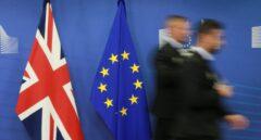 Dos empleados pasan junto a las banderas del Reino Unido y la Unión Europea.