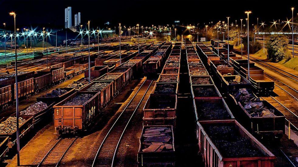 Estación ferroviaria de noche, con trenes de mercancías.