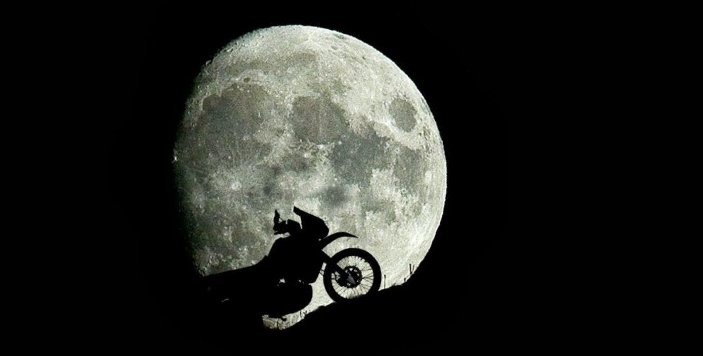 Una moto frente a la luna casi llena