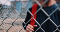 Un niño tras la valla de un patio de colegio.