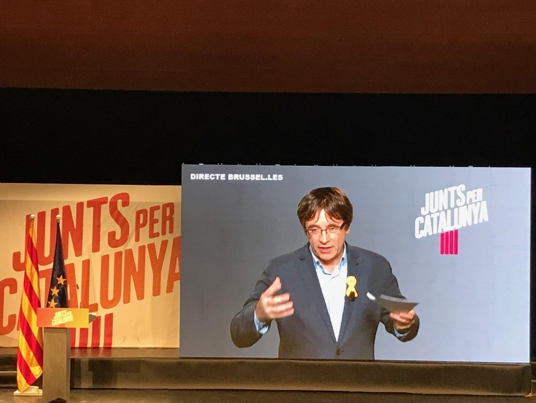 Puigdemont interviene por videoconferencia en un mítin de Junts per Catalunya.