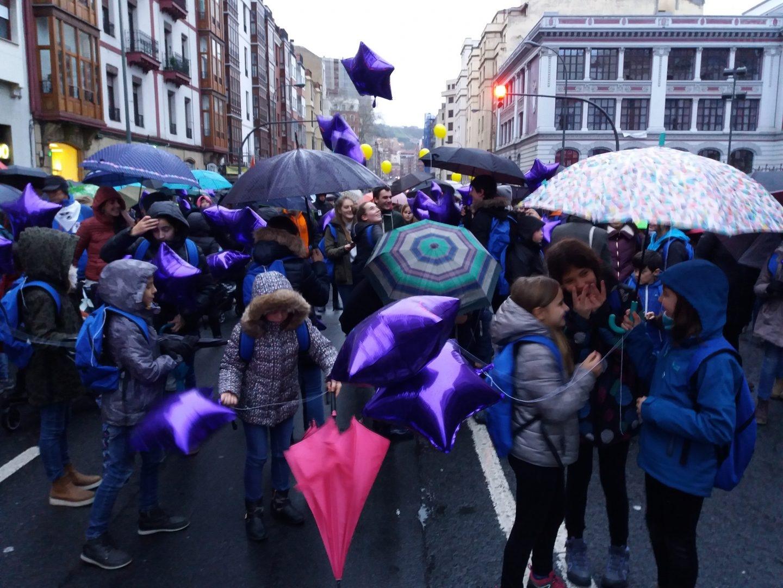 En la cabecera de la manifestación un grupo de niños, con mochila y globos lila, conversa minutos antes del inicio de la marcha.