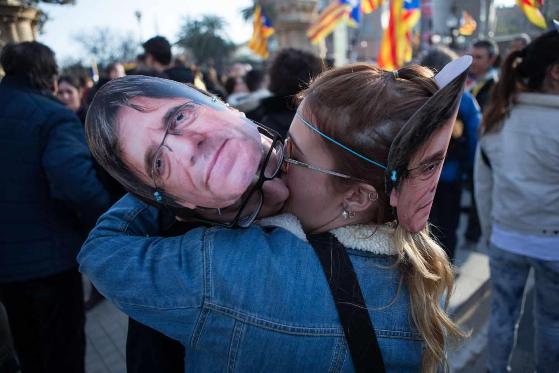 Una manifestante besa una careta de Puigdemont.