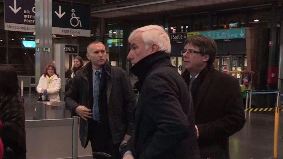 Luis Escola (al fondo), junto a Carles Puigdemont y el empresario Matamala, a punto de embarcar en dirección a Copenhague (Dinamarca).