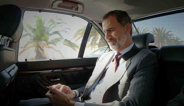 El Rey Felipe consulta el móvil en el coche oficial.