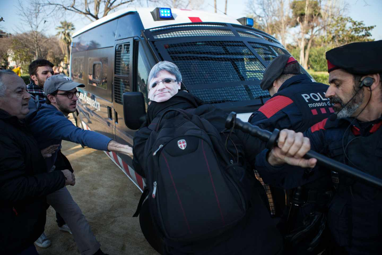 Los Mossos tratan de contener a los manifestantes, algunos con caretas de Puigdemont, que tratan de irrumpir en el Parlament.