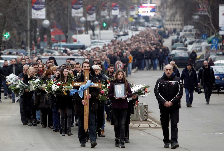 Residentes de la cuidad kosovar de Kosovska Mitrovica participan en una procesión de familiares y allegados en despedida del líder serbokosovar Oliver Ivanovic.