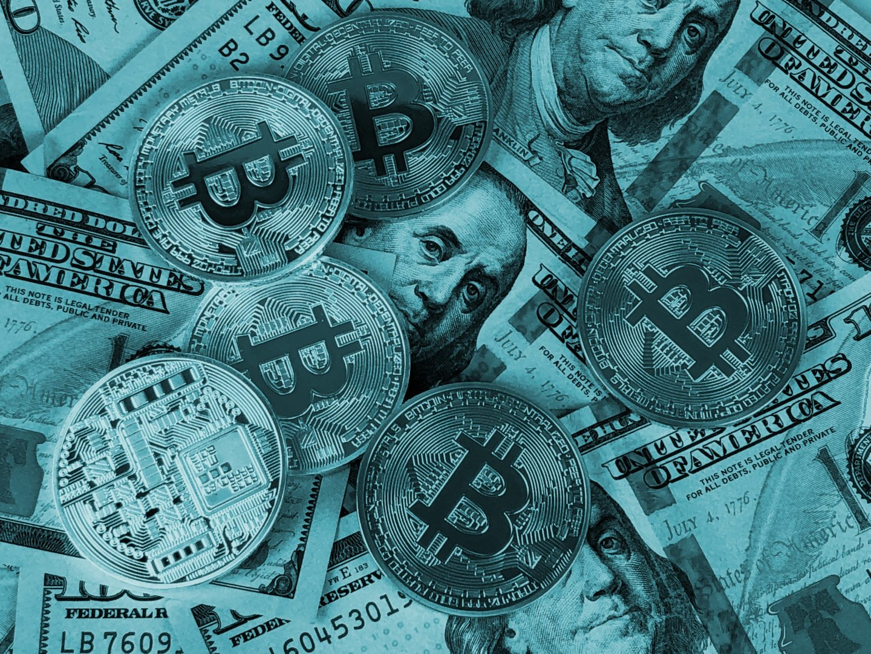 Representaciones de la moneda virtual bitcoin sobre billetes de dólar.