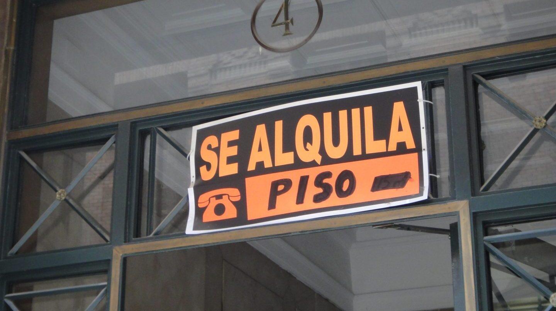 Cartel con el eslogan de 'se alquila' en el portal de un edificio.