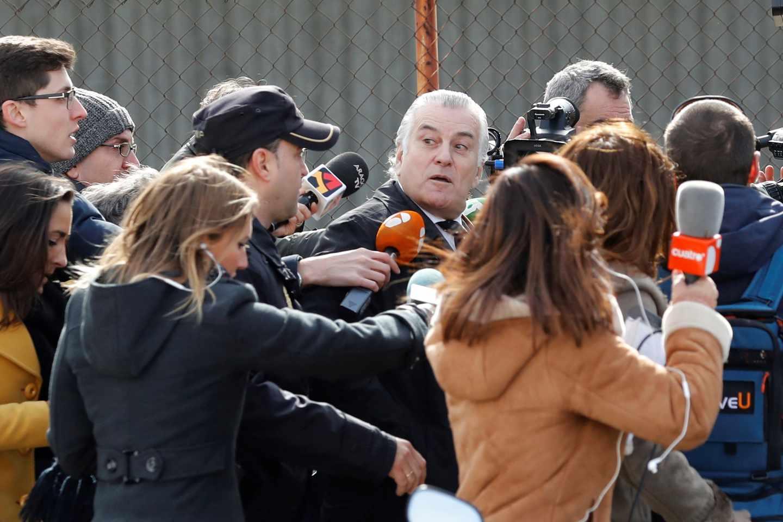 Luis Bárcenas abandona la Audiencia Nacional rodeado de periodistas.