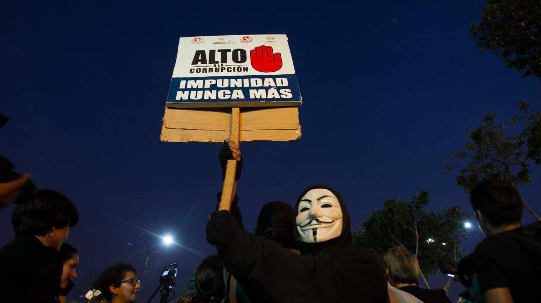 Un manifestante muestra un cartel contra la corrupción política en Lima.