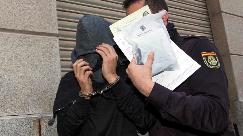 Un policía conduce a un detenido en la jefatura de la policía nacional de Murcia.