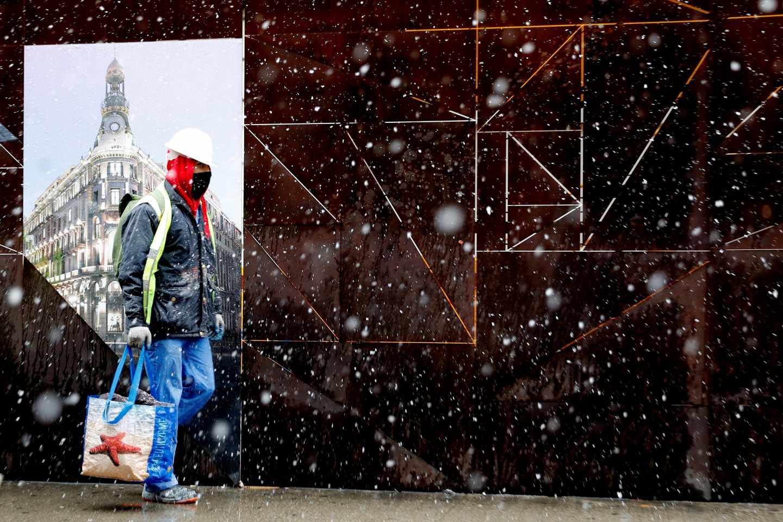 Un hombre camina bajo la intensa nevada caída esta mañana en el centro de la capital. La nieve que cae desde primera hora de la mañana en la Comunidad de Madrid ha cuajado en torno al mediodía en la capital, donde a estas horas el blanco es el color predominante en puntos como el parque de El Retiro y los alrededores del río Manzanares. La Ciudad Universitaria y el aeropuerto Adolfo Suárez Madrid-Barajas son otros de los rincones donde ha cuajado la nieve, mientras que en la Plaza Mayor, la Gran Vía o en la Puerta del Sol aún no lo ha hecho por el intenso tránsito de peatones y coches, y a la humedad de la calzada.