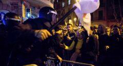 Un agente de los Mossos d'Esquadra recoloca una de las vallas que los manifestantes trataban de echar abajo.