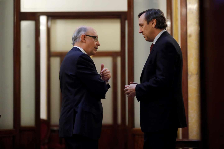 El ministro de Hacienda, Cristobal Montoro, y el portavoz parlamentario del PP, Rafael Hernando, en los pasillos del Congreso.