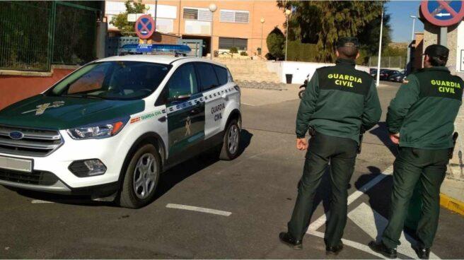 Dos agentes de la Guardia Civil frente a un coche del cuerpo.