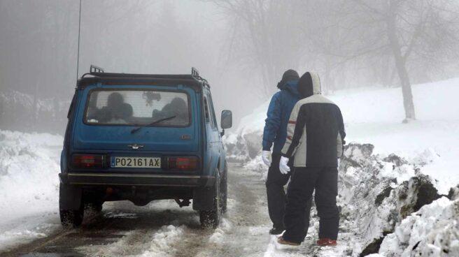 Un coche circula por una carretera nevada en Lugo.