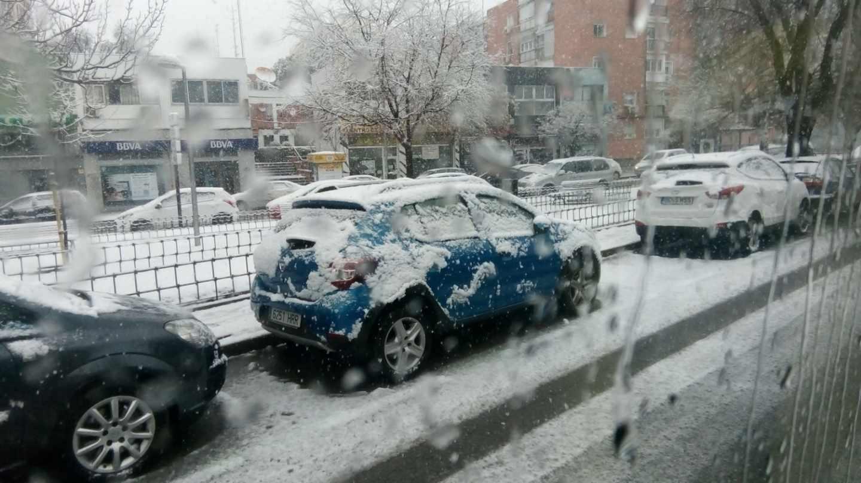 Un coche completamente nevado en Madrid.
